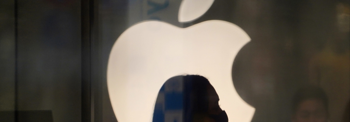A employee wearing a protective mask is silhouetted while standing in front of an Apple Inc. logo at the company's store, temporarily closed due to the coronavirus, in the Ginza area of Tokyo, Japan, on Sunday, March 15, 2020. Apple Inc. said on March 14 it's closing its hundreds of retail stores outside of Greater China until March 27 and is moving to remote work in order to help reduce the spread of coronavirus. Photographer: Toru Hanai/Bloomberg via Getty Images